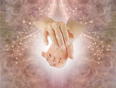 Shamanic Energy Healer sending healing - female healer with cupped hands against a gently sparkling natural pink brown ethereal background