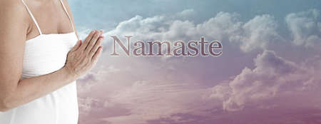 Namaste Buddhism greeting message background - female in white dress with hands in prayer position at heart level with the word NAMASTE against a beautiful cloud sky background