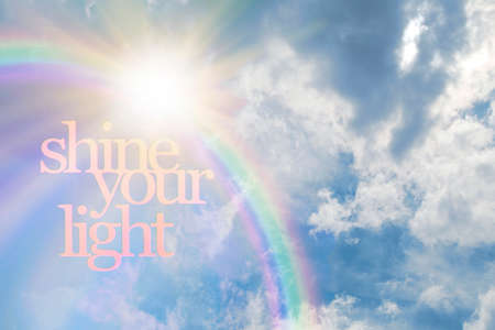 Shine Your Light Rainbow Sunshine Cloud Concept - beautiful fluffy cloudscape background with a rainbow broken by bright sunburst and the words SHINE YOUR LIGHT with copy space Zdjęcie Seryjne - 160002015