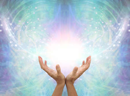 Connecting to High Resonance Healing Energy - female cupped hands reaching up into a beautiful white light and green blue  energy field background with shimmering sparkles and white light flowing