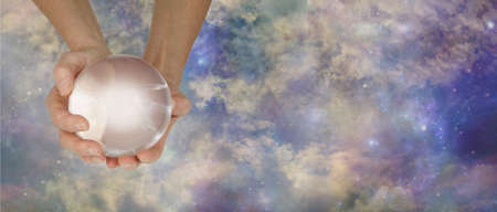 Ask the crystal ball any question website banner concept - hands holding a large clear crystal ball against an ethereal multicoloured celestial heavenly sky background with copy space