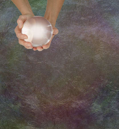 Fortune Teller's Message Board Background - female hands holding a large clear crystal ball  on a rustic dark grunge  background with copy space for messages
