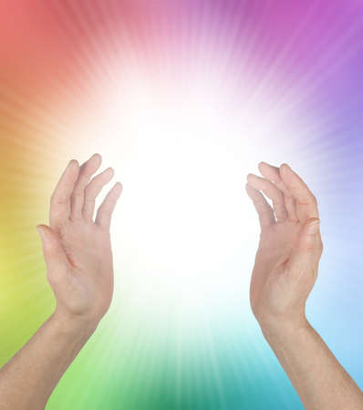 Healing Rainbow Energy Phenomenon and White Light - female hands with a bright white orb between and rainbow coloured aura with copy space