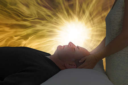 Channelling Beautiful Golden Healing Energy  - female with hands gently holding man's head, laid supine, with a vibrant white light lighting up his face surrounded by golden light and copy space Zdjęcie Seryjne