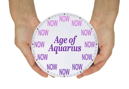 The Age of Aquarius is NOW concept - female hands holding a clock face with the numbers replaced by 12  NOW words and in the centre the words AGE OF AQUARIUS on a white background Zdjęcie Seryjne - 161762756