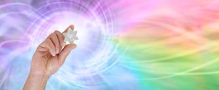 The incredible energy a Merkabah emits - male hand holding a white quartz Merkabah polished crystal emitting a stunning multicoloured rainbow vortex with copy space