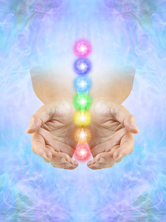 Sending You Chakra Healing Energy -  cupped hands emerging from ethereal blue energy field with a column of Seven Chakras floating between hands and copy space below