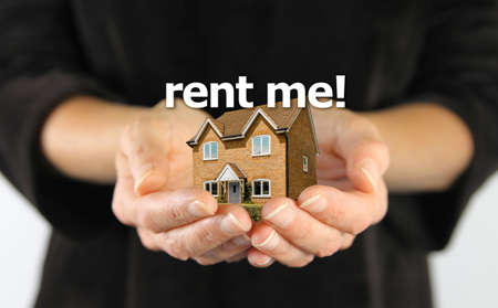 Landlord with house to rent concept female hands holding a miniature house in cupped hands with the words RENT ME floating above. Zdjęcie Seryjne