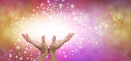 Connecting to High Frequency Reiki Universal Healing Energy - female cupped hands reaching up into a beautiful white light against a gold and pink energy field background with sparkles and white light