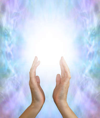 Sending out gentle spiritual healing energy  - female hands reaching up into a white energy field against a jade green purple energy formation background and copy space