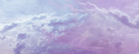 Beautiful romantic pink blue ethereal cloudscape panoramic banner - wide sky line panorama with a romantic pale pink and purple blue puffy cloud stream