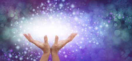 Connecting to High Frequency Universal Healing Energy - female cupped hands reaching up into a beautiful white light against a purple green blue energy field background with sparkles and white light