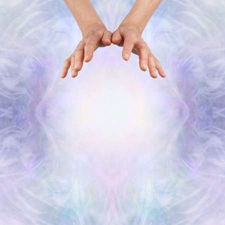 Energy healer sending out high vibrational energy - female healing practitioner using intention to send high frequency energy where it is needed on lilac background with copy space Zdjęcie Seryjne