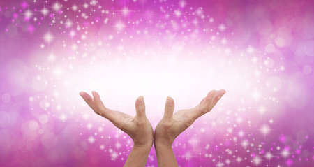 Connecting to High Frequency Magenta Universal Healing Energy - female cupped hands reaching up into a beautiful white light against a pink energy field background with sparkles and white light Zdjęcie Seryjne