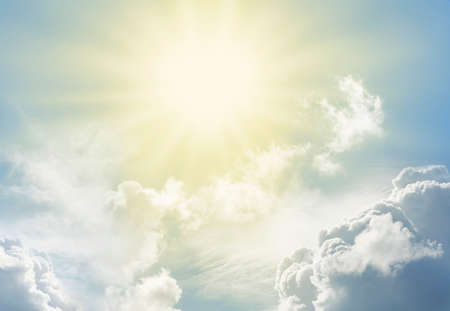 Beautiful Heavenly Easter Sunburst - Blue sky and big fluffy cumulus clouds with a bright pale yellow sunburst ideal for religious and spiritual themed backgrounds