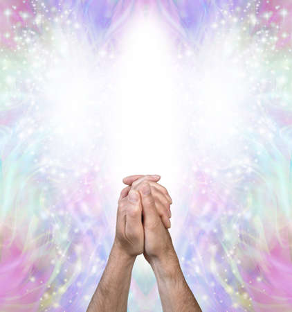 Praying for help from the Angelic Realms - male hands clasped in prayer position against a bright white Angel form and beautiful pale multicoloured spiritual energy behind