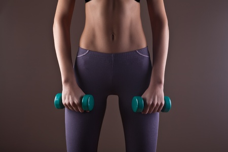 Girl with a perfect body engaged in fitness with weights Stock Photo