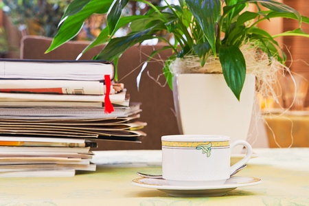 cup on a table with papers and newspapers