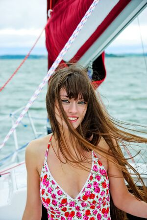 Beautiful girl in light dress standing on the deck of sailboat photo