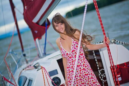 Beautiful girl in light dress standing on the deck of sailboat Stock Photo