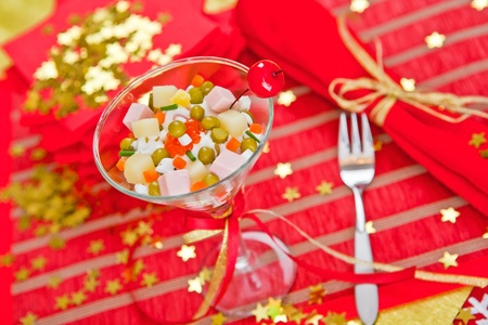 Beautifully decorated portion of Russian salad stands on the holiday table photo