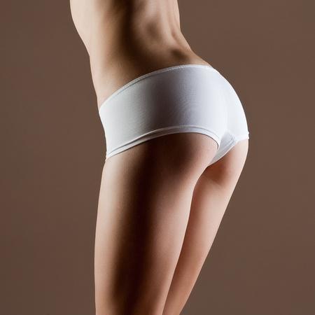 petite fille maillot de bain: Beaut� et de la femme parfaite avec le corps de fitness id�al en culotte blanche Banque d'images