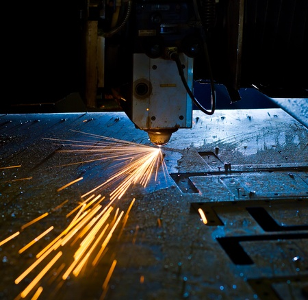 Laser cutting with sparks close up photo