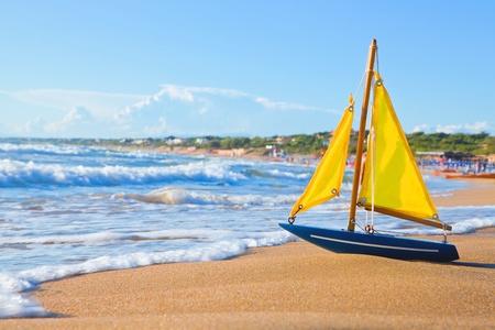 Le bateau est petit jouet sur la plage sablonneuse