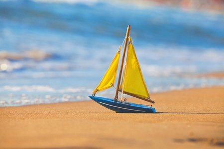 The little toy boat stands on sandy beach photo