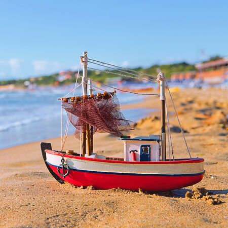 The little toy boat stands on sandy beach
