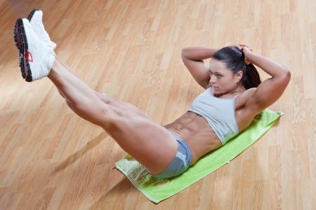 tummy: Beautiful athletic trainer shows examples of exercises in the gym Stock Photo