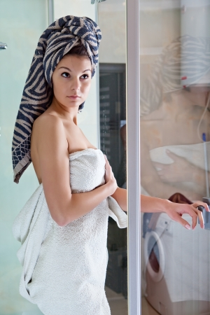 Beautiful smiling girl after a shower in a white towel Фото со стока