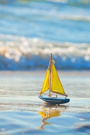 Das kleine Spielzeug-Boot steht auf Sandstrand