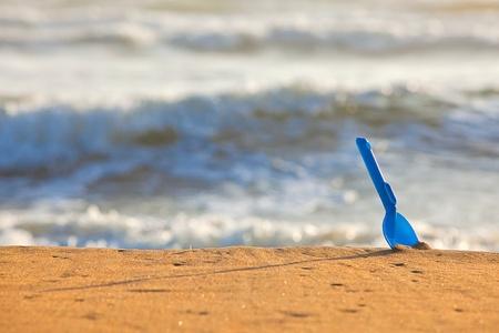 在黄色沙子的蓝色铁锹
