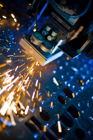 aerospace industry: Laser cutting with sparks close up