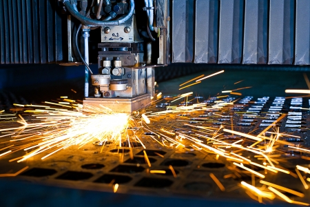 machine: Laser cutting with sparks close up