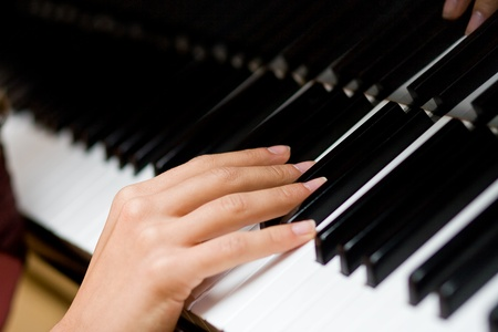 La femme douce la main sur les touches du piano Banque d'images
