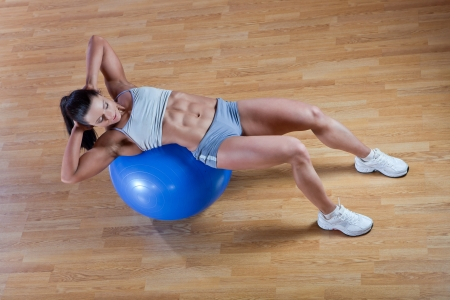 Beautiful athletic trainer shows examples of exercises in the gym photo