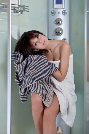 Beautiful smiling girl after a shower in a white towel photo