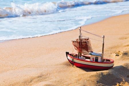 Le petit bateau de jouet tient sur la plage de sable Banque d'images