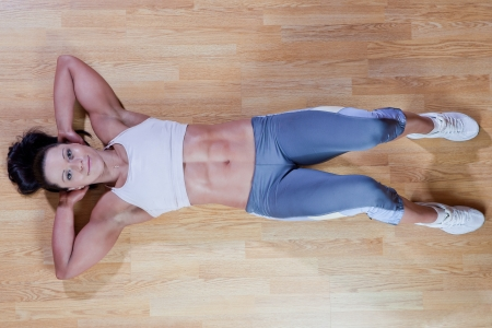 Beautiful athletic trainer shows examples of exercises in the gym Stock Photo
