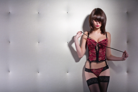 Seductive woman in a corset and stockings standing in front of white wall Stock Photo