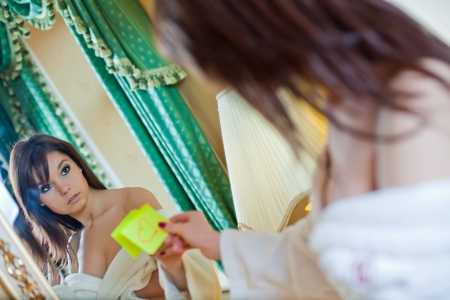 Beautiful girl in a bathrobe sticks the note with heart on the mirror Stock Photo