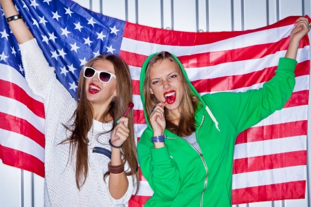 Two beautiful girls with red lollipops holding a flag of the USA
