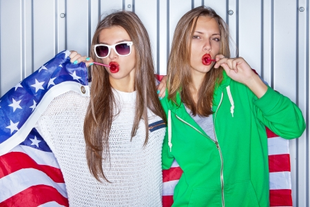 Two beautiful smiling girls with red lollipops holding a flag of the United States photo