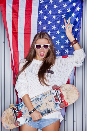 Beautiful girl with a skateboard in front of a flag of the U. S. Фото со стока