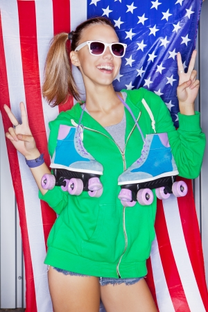 Beautiful girl with a roller skates in front of a flag U. S. waving flag Stock Photo