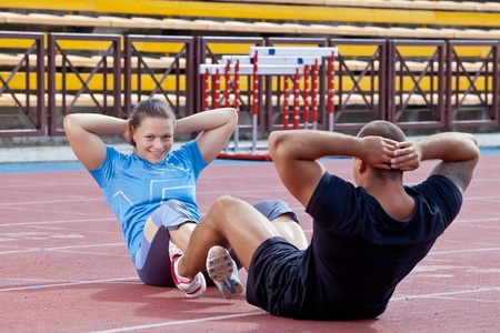 Two athletes help each other to pump the abdominals at the stadium