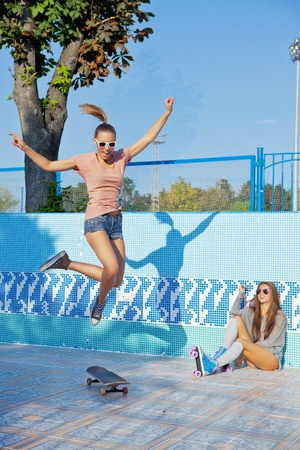 two beautiful young girls in an empty pool, one watches the other making trick on the scateboard photo