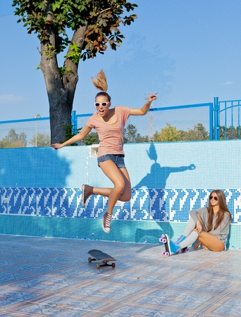 two beautiful young girls in an empty pool, one watches the other jumping over the scateboard Stock Photo